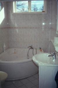 Badrum/toalett med jacuzzi-badkar vilken ibland på grund av vattentillgång måste användas sparsamt.